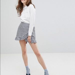 Wrap front gingham mini skirt with ruffle trim